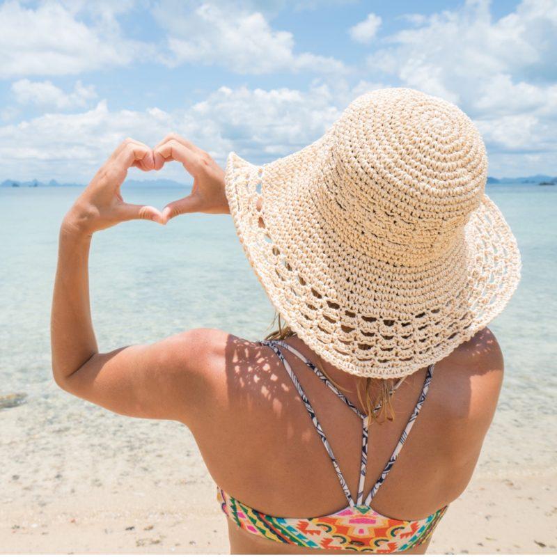 Frau macht Herz an einem tropischen Strand; coole Geschenke & witzige Geschenkideen für Weltendecker